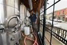 Brewer Aaron Fries cleans the beer storage tanks at North Country Brewing on South Main Street in Slippery Rock.