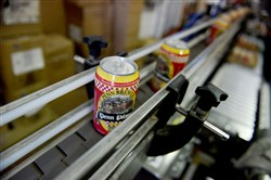 In this 2016 photo, cans of beer travel down an assembly line as Penn Brewery contracts Buckeye Mobile Canning  to can cases of Penn Pilsner.