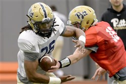 Chawntez Moss takes a hand-off from Ryan Adzima during Pitt's March 29 workouts on the South Side.