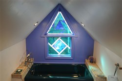 The stained-glass window that set the color palette for Robin Alexander's third-floor renovation in Perry Hilltop. She had the bathtub painted teal to match.