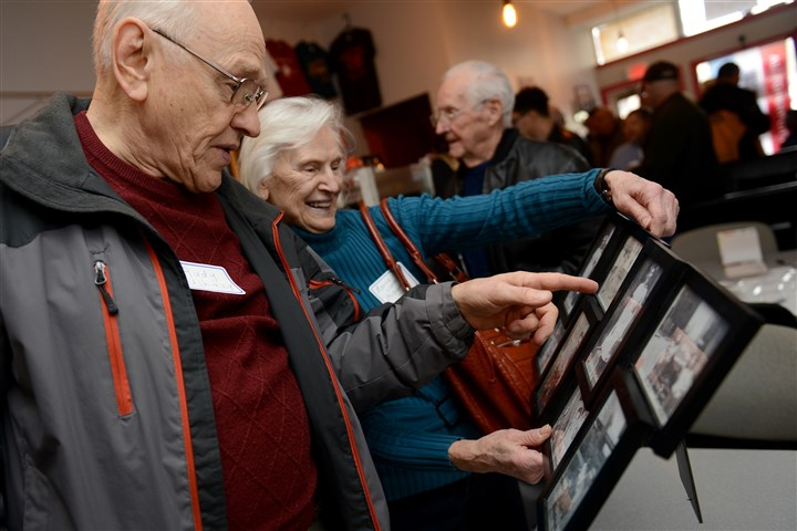 "20160409ppWardReunion1SUNLOC-5 Rudy Ujhazy, 83, looks over a display of photographs from ""the Ward"" with his sister, Maggie Ushazy McDonough, 82, at the first reunion of the Hope Harveys Football Club on Saturday at the Allegheny City Historic Gallery on East Ohio Street. The Hope Harveys began in what was then known as Pittsburgh's First Ward and commonly known as ""the Ward,"" which encompassed what is now called the North Shore."