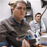 In an undated handout photo, Nick Annetta, right, watches as Ian Burkhart, who is paralyzed from the neck down, uses his right hand to play a video game.