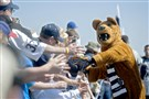 The Penn State Nittany Lion mascot high-fives fans as the team arrives at Beaver Stadium for the Blue-White spring game.