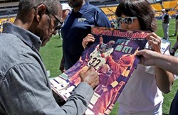 Former Pitt star Tony Dorsett signs a Sports Illustrated poster from 1977 for a fan before the start of this year's spring game at Heinz Field.