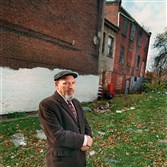 Playwright August Wilson in 1999 next to 1727 Bedford Ave. in the Hill District. At the right rear are steps leading to the two rooms (later four) in which his mother raised August and his siblings.
