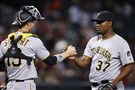 The Pirates' Arquimedes Caminero celebrates the final out with catcher Chris Stewart in the 13th inning Sunday.