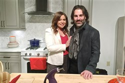Rachael Ray and her husband, John Cusimano, stand behind her kitchen island.