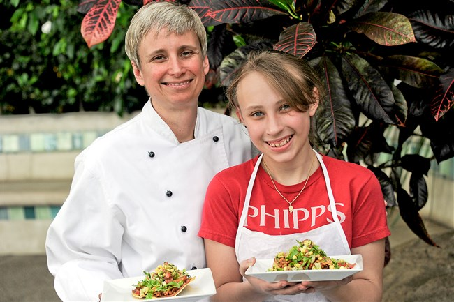Sydney Tyner, 12, prepares Chicken Taco Tower for her mom, Amy Reed, the head chef of Phipps Conservatory and Botanical Gardens.