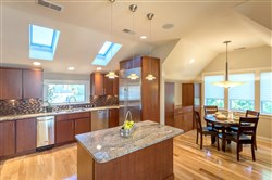 Ar view of the kitchen shows off the sub-zero refrigerator and the skylights as well as the granite countertops.