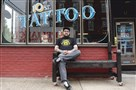 "Michael Monack sits outside 10th St. Tattoo on the South Side last month. Monack, known for his graffti tag ""MOOK"" now owns two tattoo shops."