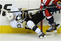 The Penguins' Conor Sheary is knocked off his skates Thursday against the Capitals.