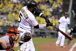 The Pirates' Josh Harrison hits a sacrifice fly scoring Starling Marte in the fifth inning against the Reds Saturday night at PNC Park.