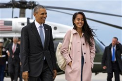 In an April 7 file photo, President Barack Obama jokes with his daughter Malia as they walk to board Air Force One from the Marine One helicopter, as they leave Chicago en route to Los Angeles.