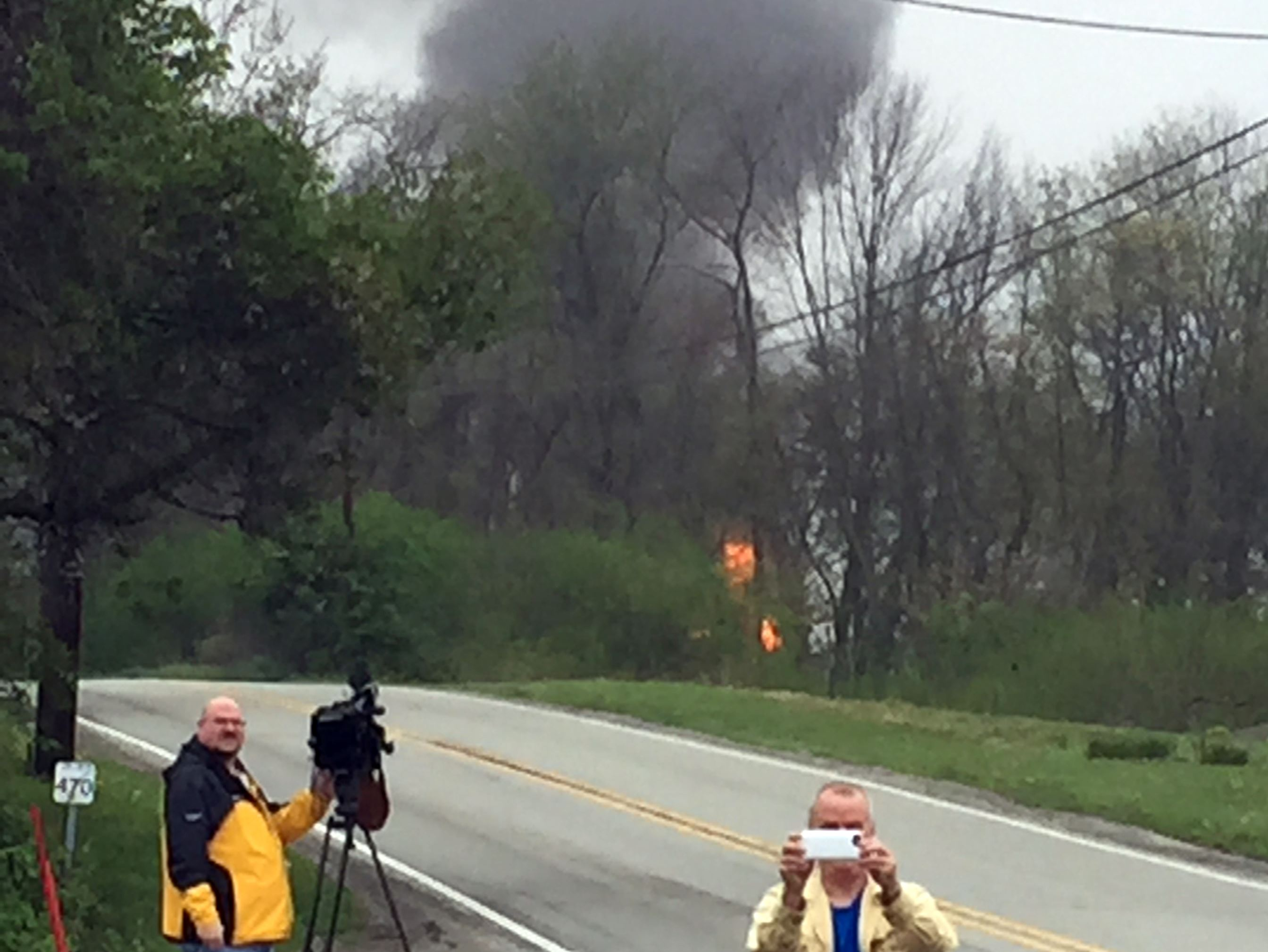 20160429dsGasWellFire3-2-2 People gather Sunday in Salem Township near the scene of a pipeline that exploded on Friday, injuring one man, damaging several homes and disrupting gas flows to the Northeast.