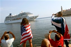 Yaney Cajigal, covered by a U.S. flag, and Dalwin Valdes, with a Cuban flag, watch the arrival Monday of Carnival's Adonia cruise ship from Miami in Havana. The Adonia's arrival is the first step toward a future in which thousands of ships a year could cross the Florida Straits, long closed to most U.S.-Cuba traffic due to tensions that once brought the world to the brink of nuclear war.