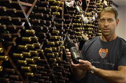 "Tony Narcisi, owner of the Narcisi Winery in Richland, holds a bottle of ""Noiret,"" their red wine."