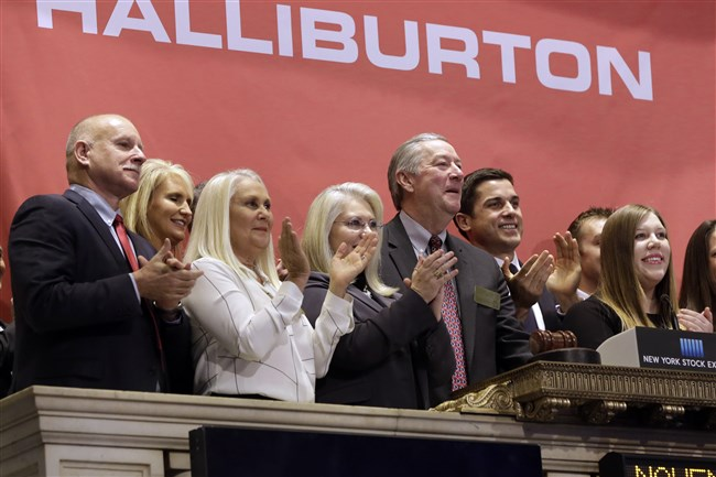 Halliburton Chairman, President and CEO David Lesar, third from right, rings the New York Stock Exchange opening bell in 2014. Halliburton and Baker Hughes, two companies crucial to the business of U.S. energy exploration, have abandoned their planned $34 billion merger, the Justice Department said Sunday.