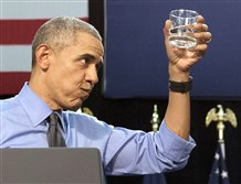 President Barack Obama holds up a glass of water as he drinks after speaking at Flint Northwestern High School in Flint, Mich., in May 2016.