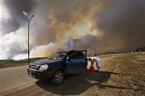 An evacuee puts gas in his car on his way out of Fort McMurray, Alberta, as a wildfire burns in the background Wednesday. The raging wildfire emptied Canada's main oil sands city, destroying entire neighborhoods of Fort McMurray, where officials warned Wednesday that all efforts to suppress the fire have failed.