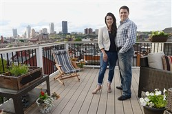 Cassandra and Tom Dixon stand on their rooftop deck, which offers views of Downtown, Oakland and the South Side Flats.