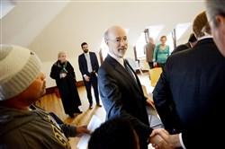 Gov, Tom Wolf walks around the room shaking hands before a roundtable discussion Thursday about Pennsylvania's opioid crisis held at the Carnegie Library of Pittsburgh's Homewood branch.