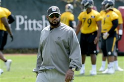Steelers coach Mike Tomlin watches players Friday at rookie minicamp on the South Side.