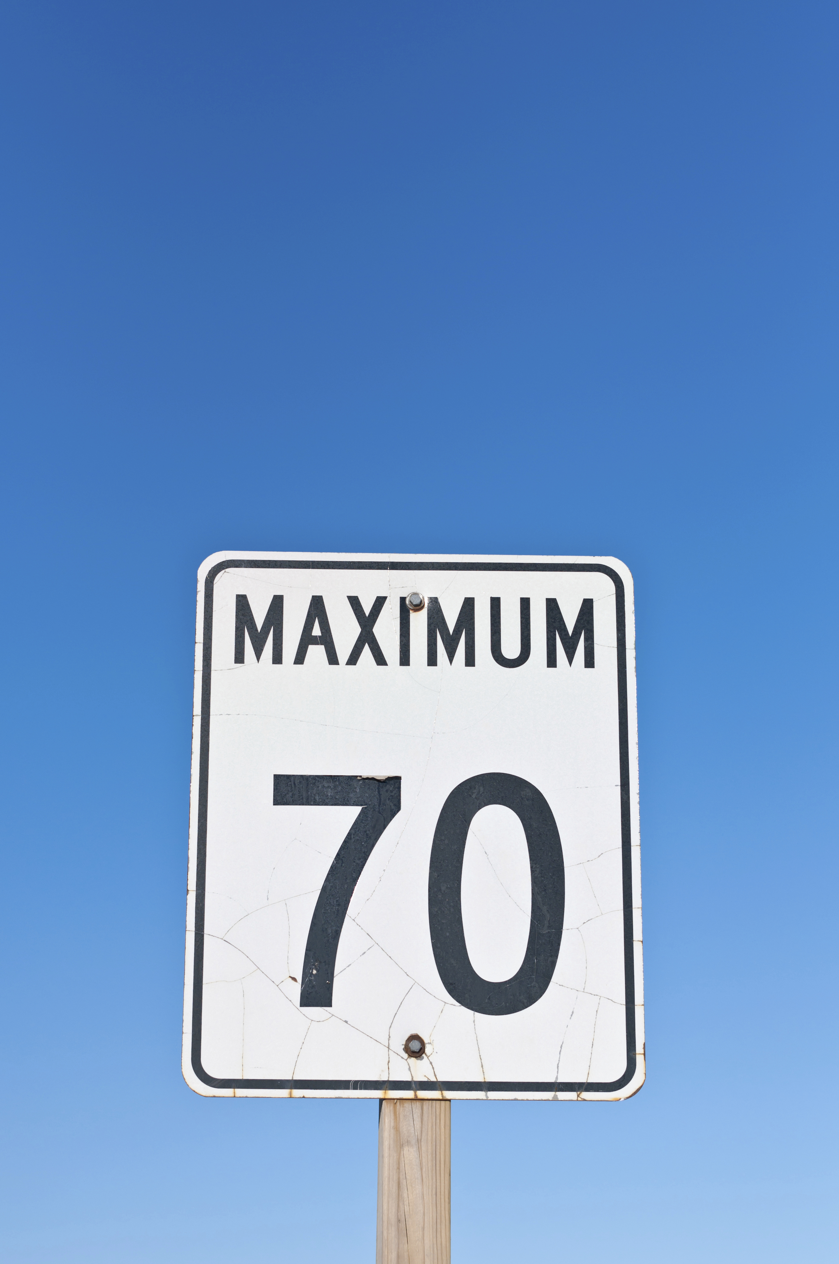 70mph A traffic sign with a cracked surface reads Maximum 70