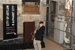 Saxophonist Lou Stellute performs Tuesday during the City of Asylum tour of the former Masonic Hall, a 20,000-square-foot building at 40 West North Ave.