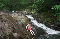 "A youth takes takes a ""bum slide"" at Rock Falls Park near Slippery Rock in Butler County after an Outdoor Extravaganza canoe trip."