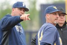 Pitt baseball coach Joe Jordano and WVU coach Randy Mazey speaks with umpires before Wednesday's game in Oakland.