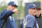 Pitt coach Joe Jordano and West Virginia coach Randy Mazey meet with an umpire before their game last season at Charles L. Cost Field.