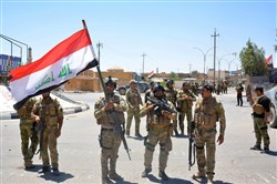 Iraqi government forces celebrate with national flags on a street Thursday in the western town of Rutba after they recaptured it from the Islamic State group.