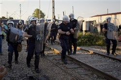 Greek police move toward a group of migrants throwing rocks, at the Macedonian border, in Idomeni, Greece, on Wednesday.