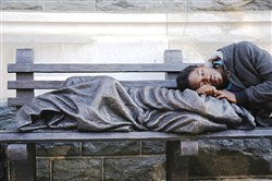 The Homeless Jesus statue serves as a pillow for a homeless man in Washington D.C.