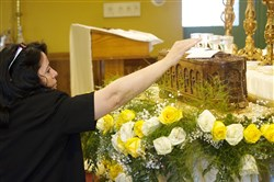 A woman who wished to remain unidentified places photographs on a box of St. Sharbel's Relics at Our Lady of Victory Maronite Catholic Church in Carnegie.