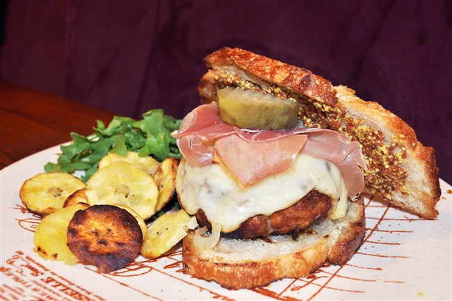 "Inspired by an annual Cuban barbecue in Pittsburgh, ""El Cubano del Lado Sur"" is a blended and seasoned beef and chorizo patty topped with a Cuban ""Mojo"" sauce, Jarlsberg cheese, Serrano ham, pickle chips and mustard on toasted sourdough."