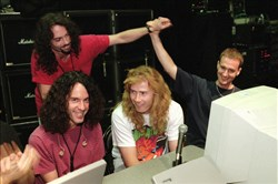 In this July 24, 1997, file photo, lead guitarist Marty Friedman, left, and lead singer/guitarist Dave Mustaine, center, field questions while bassist David Ellefson, right, high-fives drummer Nick Menza, back left, during a live chat on the Internet held at The Joint inside the Hard Rock hotel-casino in Las Vegas.