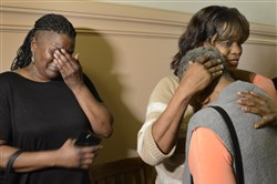 Janene Hayes, left, covers her face as she weeps while her sister Sharlene Hayes embraces their mother, Jeanette Howard, after they talked about their cousin Allen Wade at the Allegheny County Courthouse. Ms. Howard is Wade's great aunt.