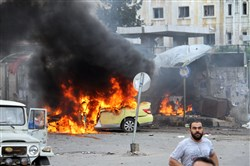 In this photo released by the Syrian official news agency SANA, Syrians gather in front of a burning car at the scene where suicide bombers blew themselves up in the coastal town of Tartus, Syria, on Monday.