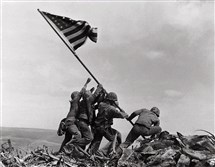 Associated Press photographer Joe Rosenthal captured this iconic image of the flag-raising at Iwo Jima on Feb. 23, 1945. The group included Marine Michael Strank, who was on the far side of the flag and can be glimpsed behind the second and third figures from the left.