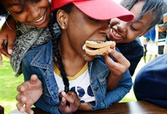 Iginah Adams, left, and Jade Shatara Baker-Wright, right, make and feed a peanut butter and jelly sandwich to Shanya Currington during a team building activity at North Park Lodge in Allison Park.