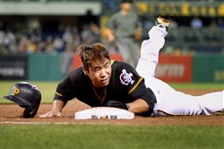 Jung Ho Kang loses his helmet as he gets back to first base safely in the first inning against the Diamondbacks Tuesday at PNC Park.
