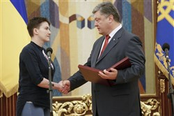 Ukrainian President Petro Poroshenko, right, shakes hands with Ukrainian jailed pilot Lt. Nadezhda Savchenko, as he awards her with the Hero of Ukraine medal in the Presidential Office in Kiev, Ukraine, on Wednesday.