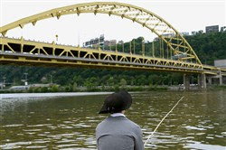 Ross Martin, summer intern at the Fort Pitt Museum, demonstrates 18th-century fishing technique with a period fishing pole on Thursday. The Point State Park museum will host a fish for Free event at the Mon Wharf Sunday.