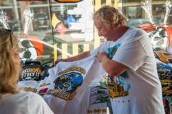 At B.A. Trading on 18th Street and Penn Avenue in the Strip District on Friday, Rich Radwanski displays a T-shirt highlighting the upcoming Penguins-Sharks matchup in the Stanley Cup Finals that begin Monday at the Consol Energy Center.