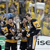 Penguins left wing Chris Kunitz, left, pose Eastern Conference trophy at the Consol Energy Center Pittsburgh Pa. Sidney Crosby (center) with Evgeni Malkin (right) and