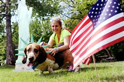 Barbara Willis of Cranberry holds onto her 7-year-old bassett hound at the annual Animal Friends Patriotic Pup Parade in North Park on Saturday.