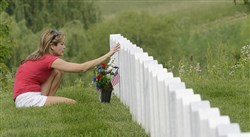 Jennifer Welsch of Carnegie touches her father's gravestone Sunday before the annual Memorial Day ceremony at the National Cemetery of the Alleghenies in Cecil, Washington County. Her father served in the Korean War.