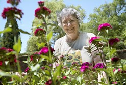 Jean Reiland, 68, of Shaler, smiles for a photo at the Shakespeare Garden in Mellon Park.