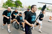 "Officer Todd Foreman of the Washington, Pa., police carries a torch Tuesday on Centre Avenue in Uptown Pittsburgh while leading members of Clairton's and Washington's police departments in the ""Be a Fan"" Torch Run. The three-day, 150-mile run from Pittsburgh to Penn State University kicks off the Special Olympics 2016 Summer Games in State College."